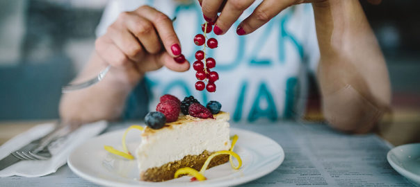 kaboompics_Woman-Enjoying-Cheese-Cake-and-a-Coffee-with-Fruits-in-a-Cafeteria